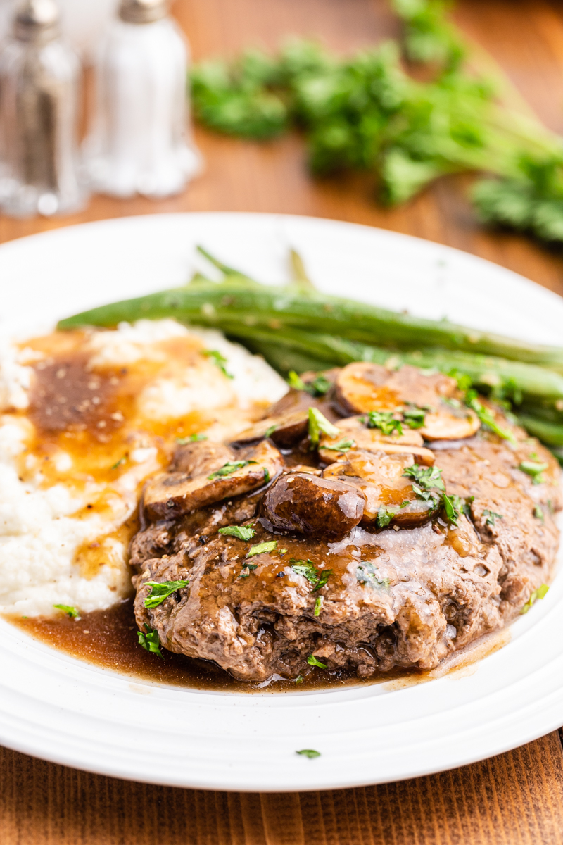 Sideview photo of Keto Salisbury Steaks with Mushroom Gravy on a white plate with mashed cauliflower and green beans.