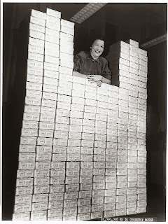Woman posed with stack of packages of $1 silver certificates at the Bureau of Engraving and Printing, Washington, D.C. [between ca. 1950 and ca. 1969] Source - loc.gov/rr/business/money/paper.html