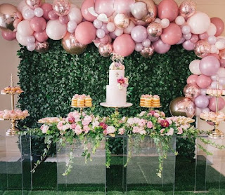Greenery backdrop with organic balloon arch and cake stand with fresh flowers