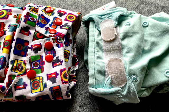 Two nappies side by side one with velcro one with poppers