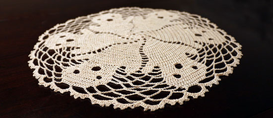 Angled view of off-white crocheted cotton ghost-motif doily on a dark background.