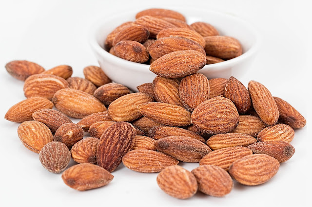Image of Almonds in large amount some are are in white bowl and some are outside bowl