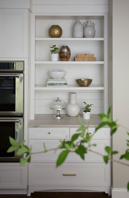 white and metallic bookshelf. styling by Patti Borrelli. Kitchen design by Kelley Vieregg. Photo by Emily Decker.