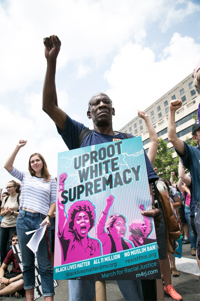image of a Black man in front of a crowd of anti-hate protesters, raising his fist into the air