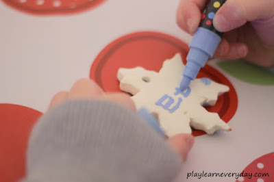 writing his name on the clay snowflake