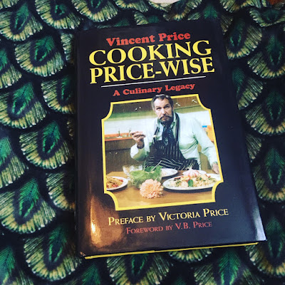 A copy of 'Cooking Price Wise' by Vincent Price laying on peacock print velvet.