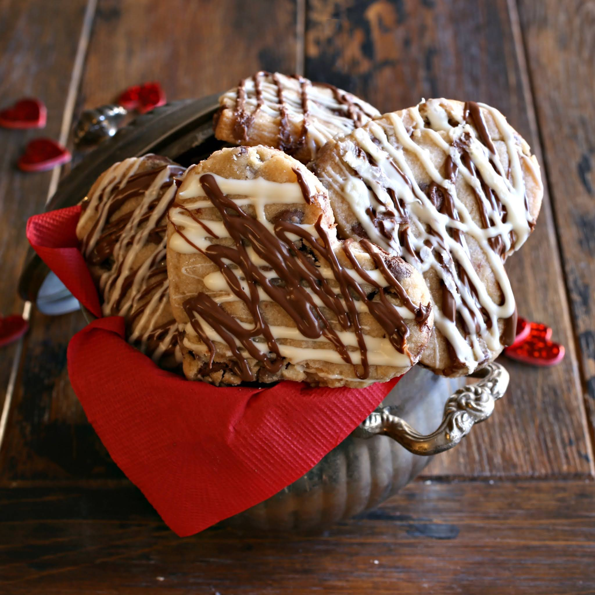 Recipe for heart shaped shortbread cookies filled with semi-sweet chocolate chips and drizzled with milk and white chocolate.