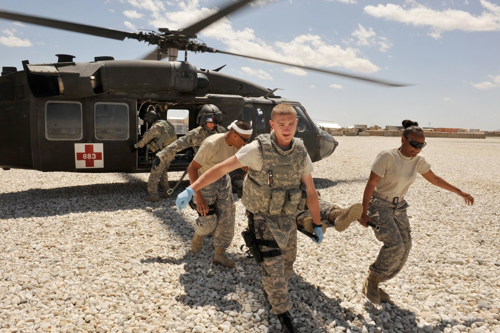 Military medical personnel remove a patient from a helicopter