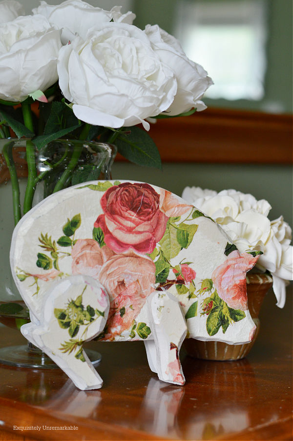 Rose Covered Pig Decor on a dresser with roses