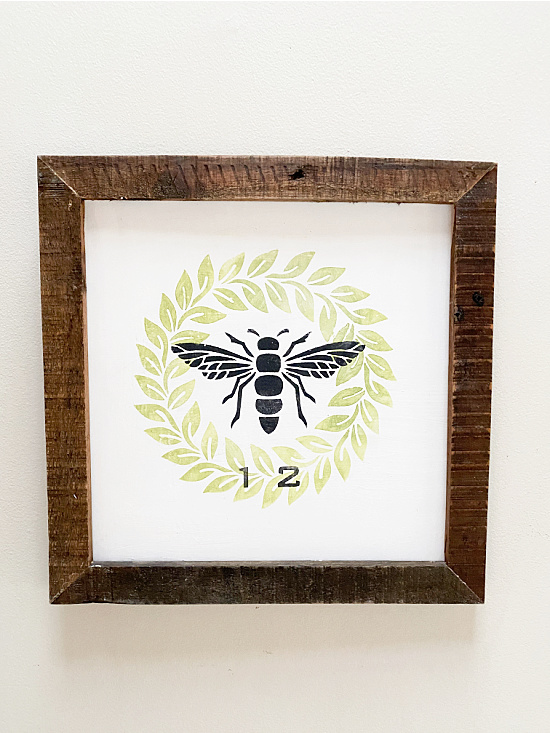 framed wreath and bee sign