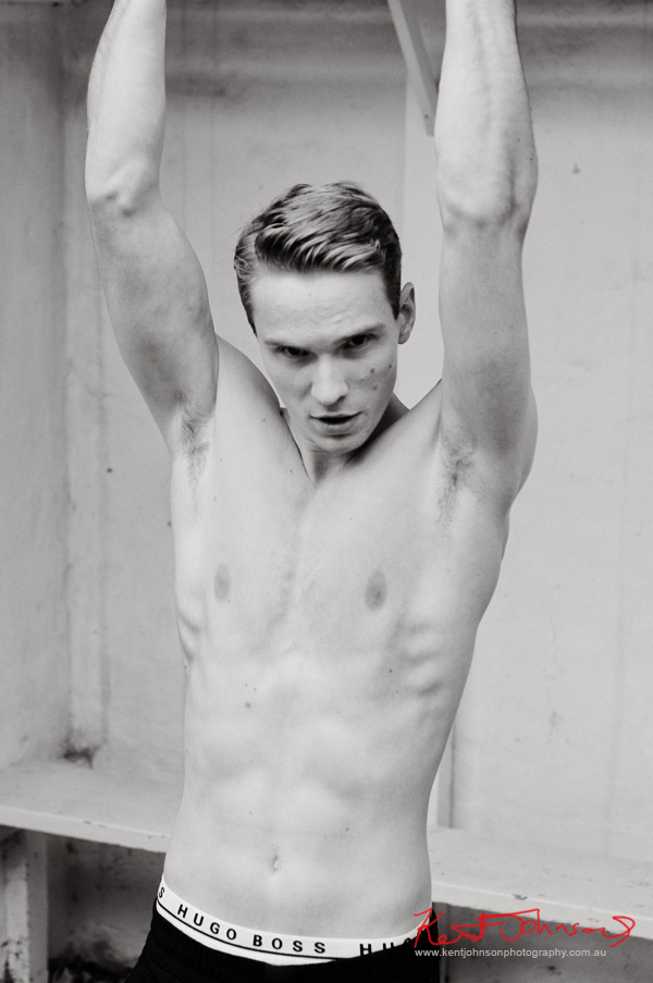 Black and White body shot doing pull-ups for a male modelling portfolio - Photographed by Kent Johnson, Sydney, Australia.