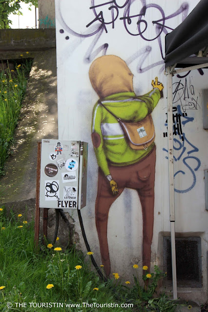 Mural of a guy with a spray can by artist Os Gemeos in Vilnius in Lithuania