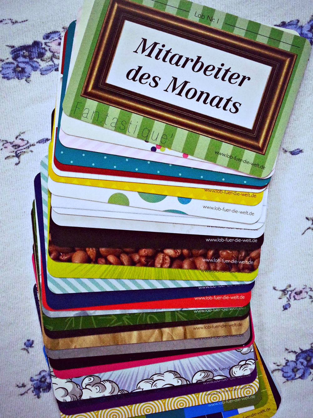 a pack of Lobkarten spread on a white piece of fabric
