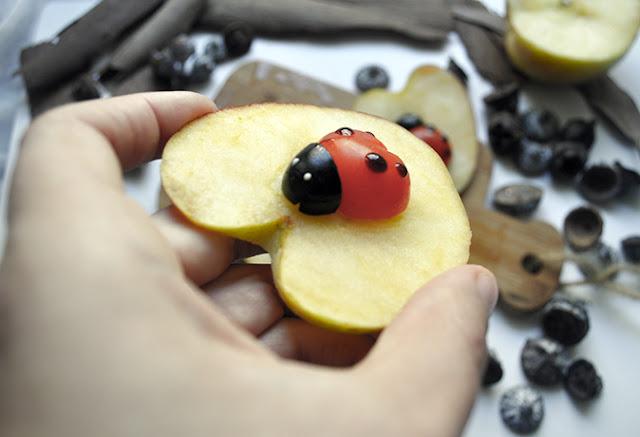una mariquita de aceituna y tomate sobre una rodaja de manzana