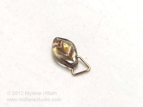 Triangle jump ring with one prong inserted into a leaf bead.