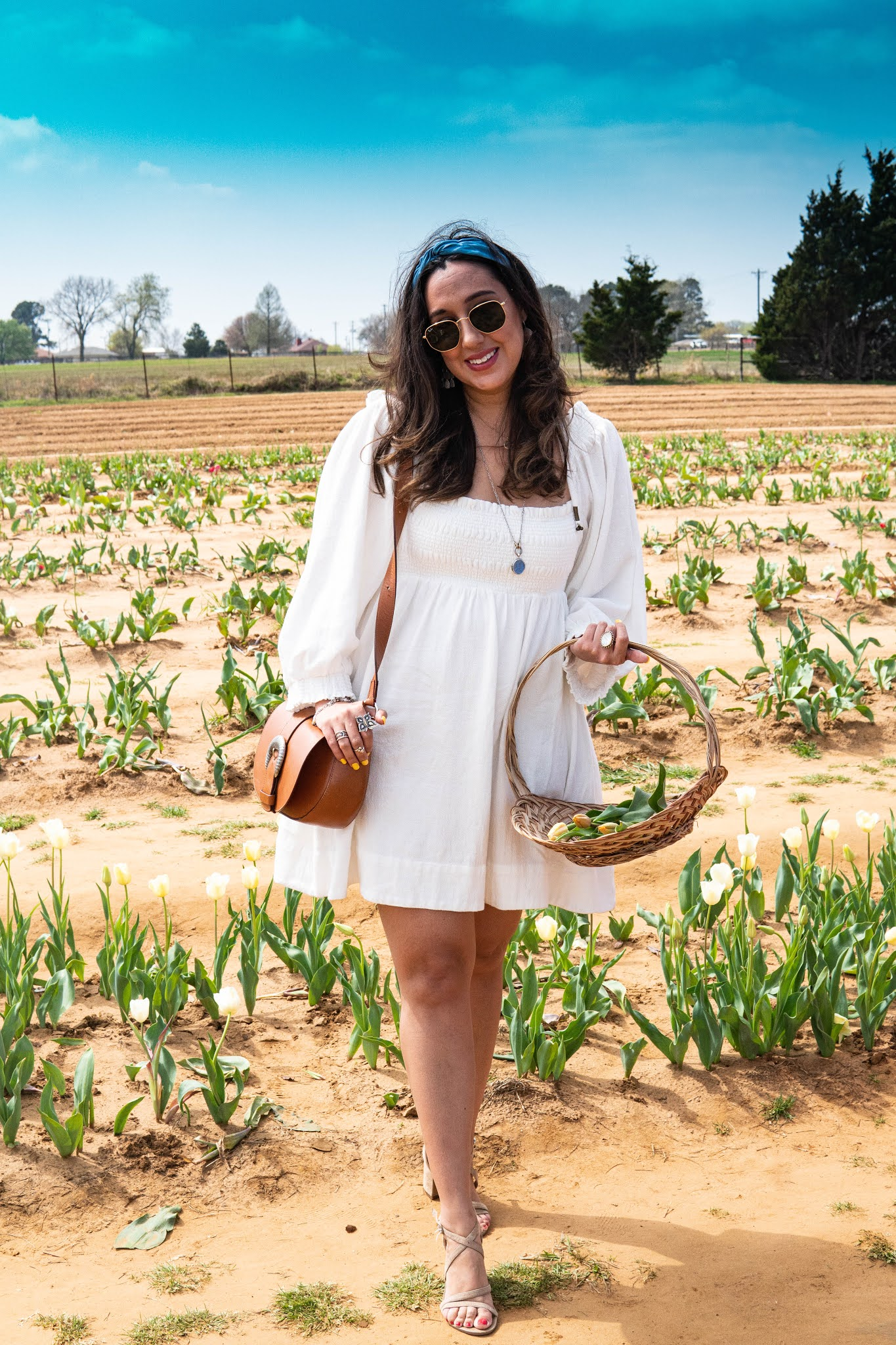 Amelia standing in a tulip field with a basket of freshly picked tulips