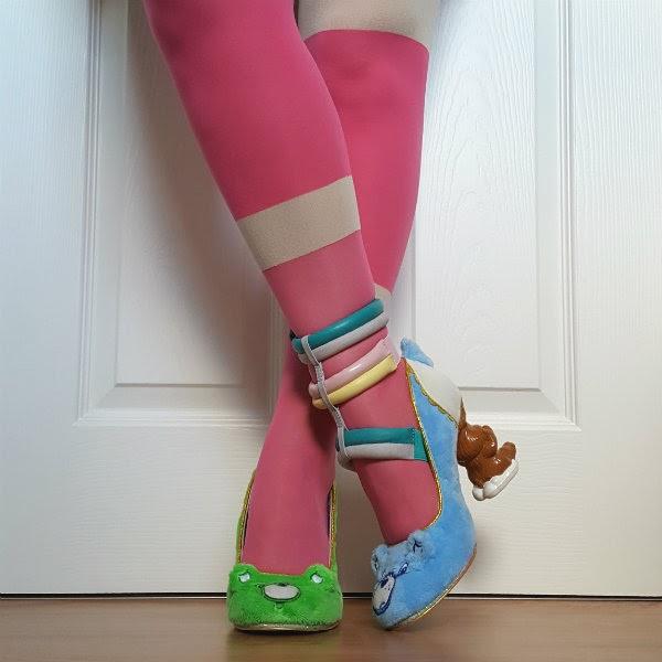crossed legs showing furry side of court shoe with care bear shaped heel