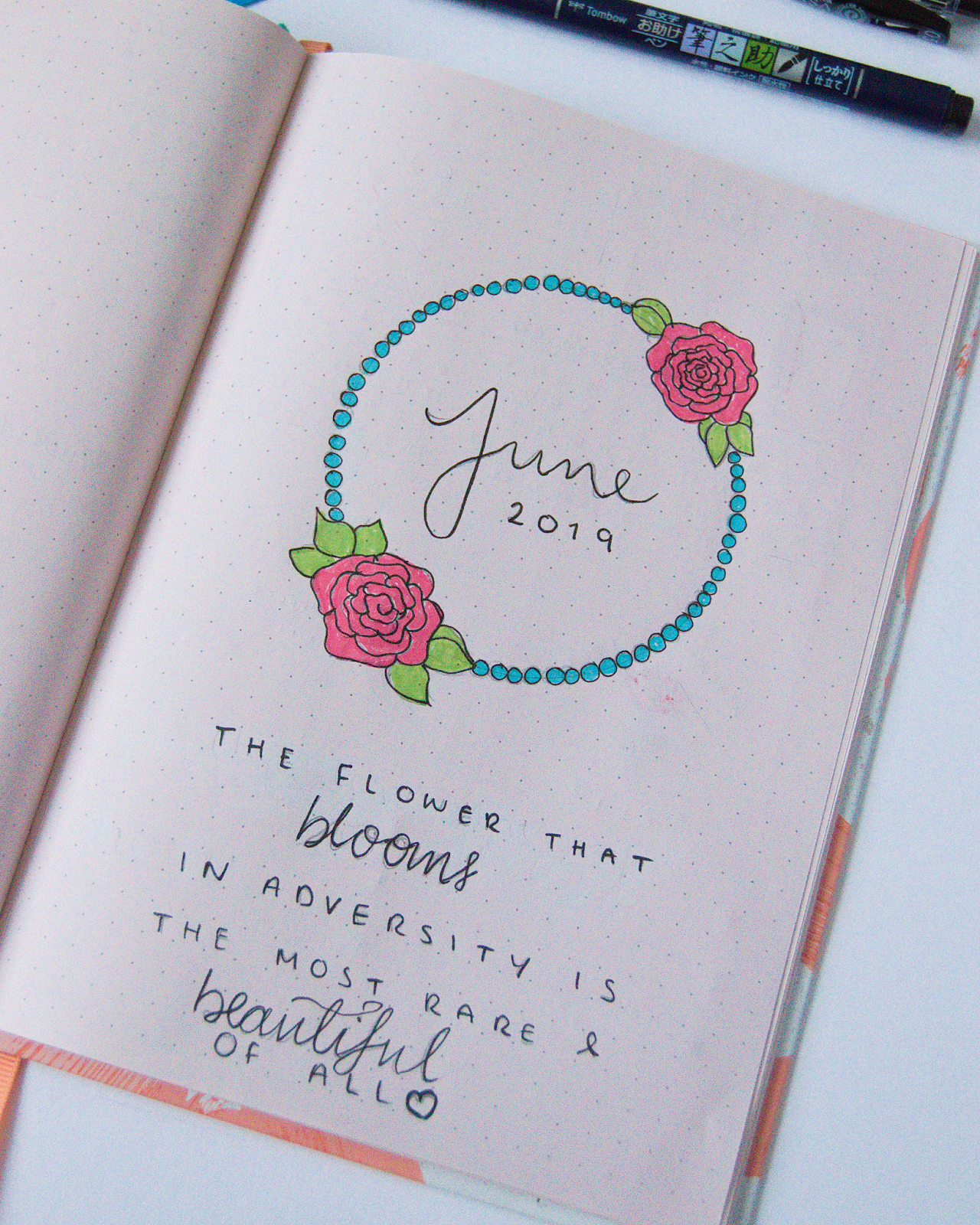 "A June title page. June if written in cursive inside a circle of blue small bubbles and two pink roses. Underneath it is written the Mulan quote ""A flower that blooms in adversity is the most rare and beautiful of all""."