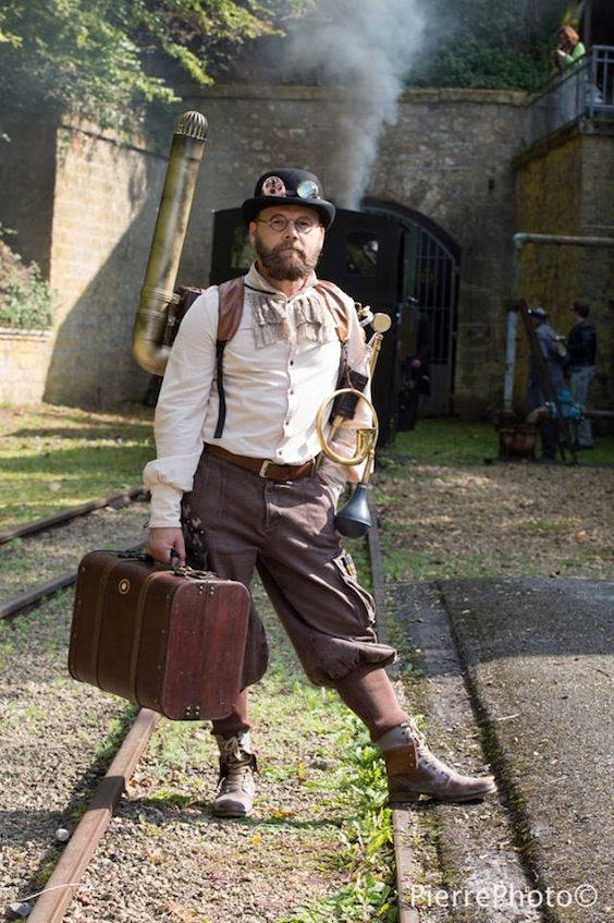 Man dressed as steampunk bartender with mobile bar in his backpack and suitcase, full of liquor and alcohol bottles and glasses. Men's steampunk costumes