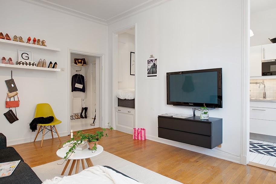 Salón con estanterías para zapatos y zona de tv