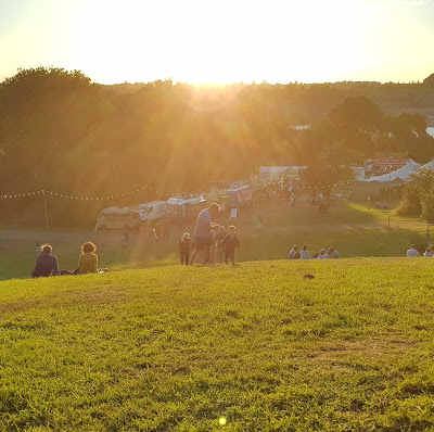 Autumnal evening view from the top of a hill, as the sun sets over a festival scene, with people sitting on the hill below