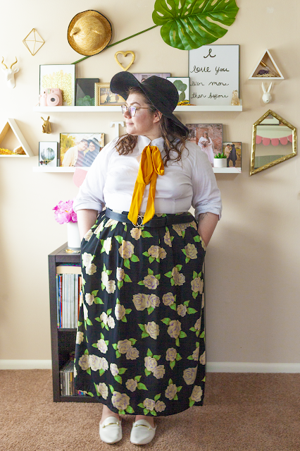 An outfit consisting of a black floppy hat, a white button down blouse with a yellow ribbon tied under the collar tucked into a white flower with green leaves flower motif on a black maxi skirt and white mules.