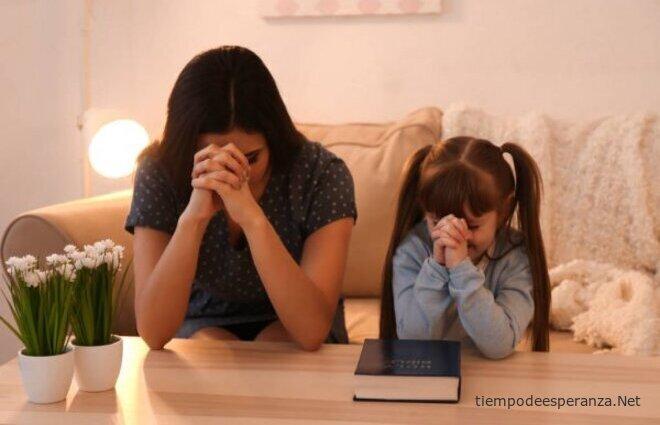 Madre e hija orando con Biblia