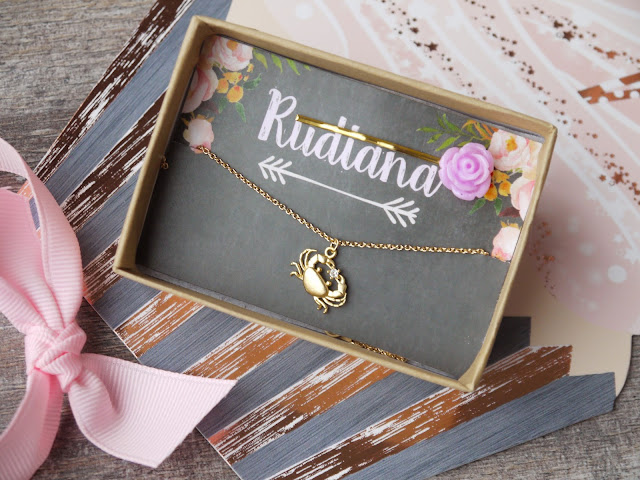 a gold necklace with a tiny crab holding a diamante