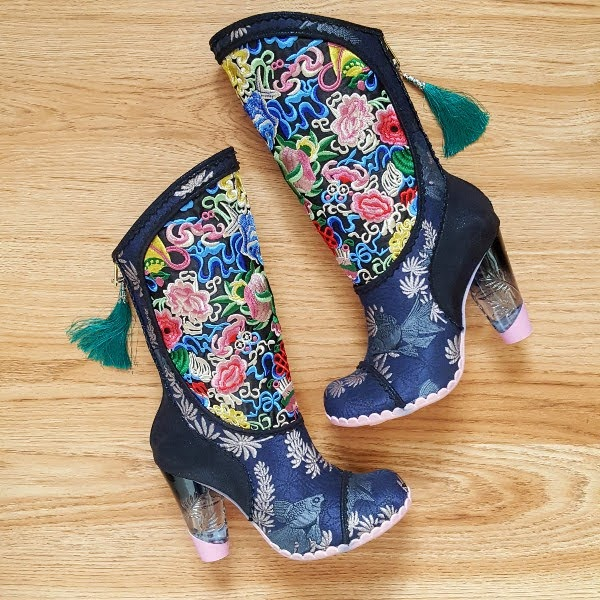 pair of navy and floral embroidered boots lying on floor with green tassel zip detail
