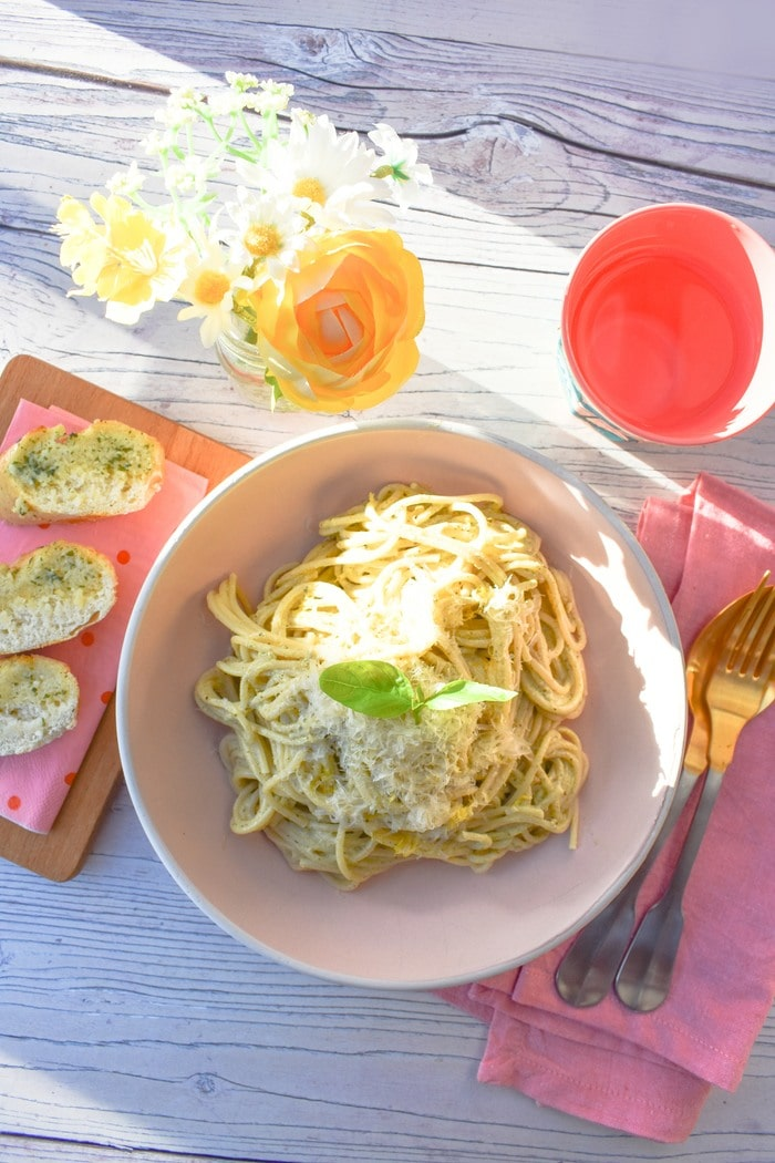 Overhead shot of Creamy Lemon Basil Spaghetti in pasta bowl served with garlic bread on a wooden slab