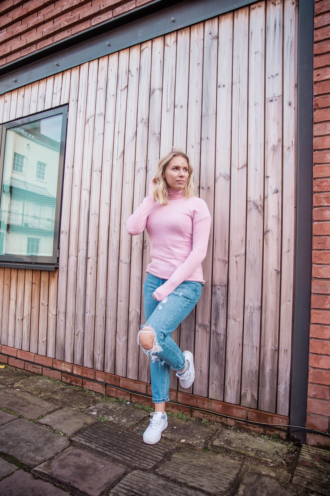 Rachel Emily standing in front of a wood clad wall in a pink top and blue jeans