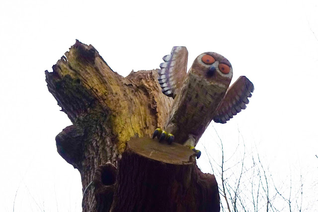 A wooden carved owl in tree