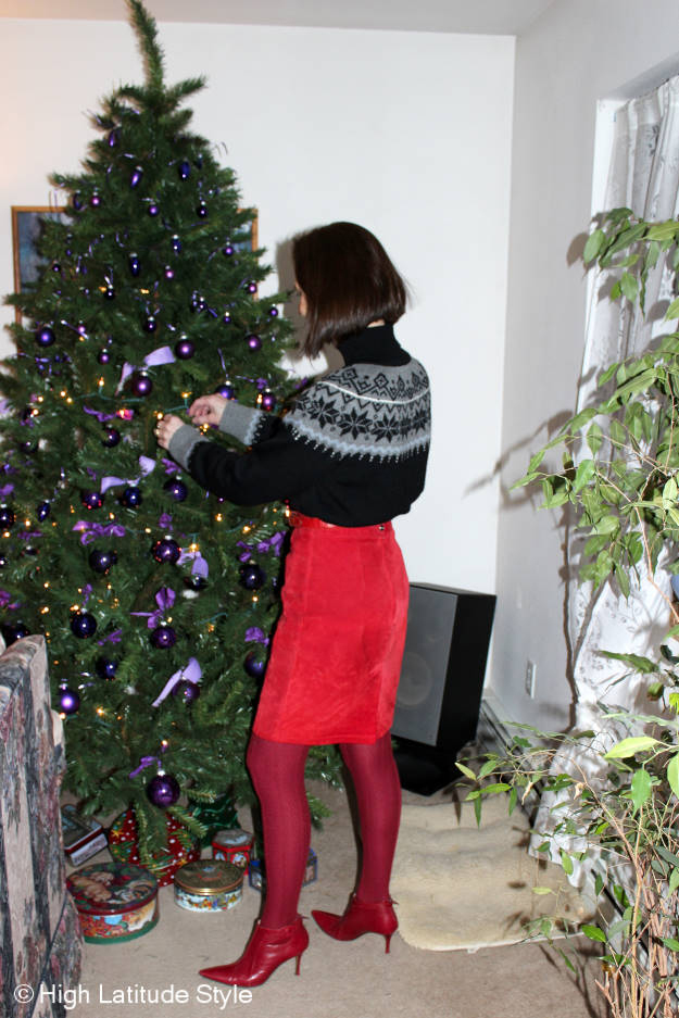 image showing a woman decorating a real Christmas tree with purple baubles