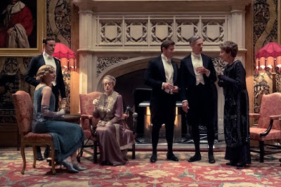 Movie still for Downton Abbey film where the Crawley family (including Penelope Wilton, Maggie Smith, Harry Hadden-Paton, Matthew Goode) sits around the fire having a drink