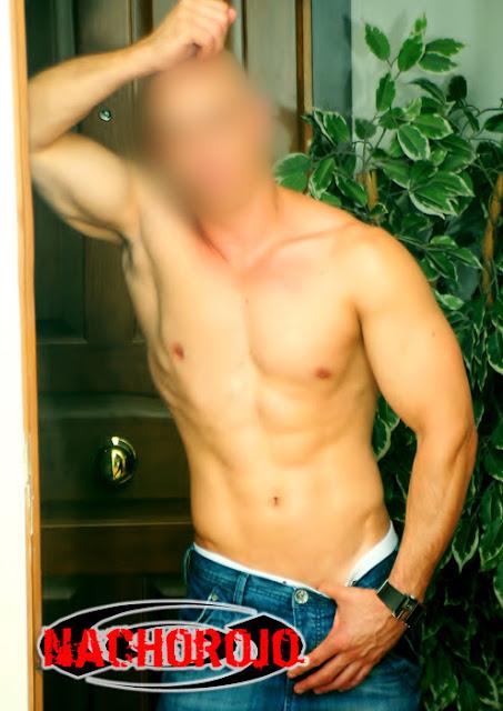 escort masculina bajo puerta de apartamento sin camiseta