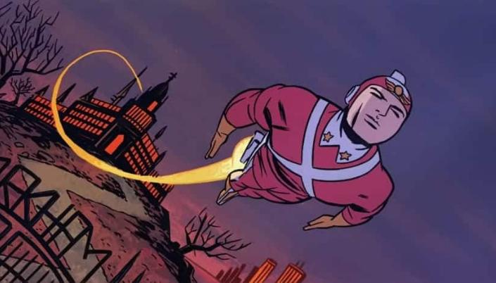 Imagem: um personagem com um traje vermelho com um x branco no peito, um capacete em formato de foguete, deixando um rastro de fogo desde uma enorme mansão preta com janelas laranja e abaixo um portão de ferro com o nome Gotham nela, e um fundo de pôr-do-sol.