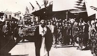 Ο π. Σταύρος Καρπαθιωτάκης με τον σταυρό προπορεύεται της πομπής   συνοδεύοντας την σορό του Νίκου Καζαντζάκη το 1957.
