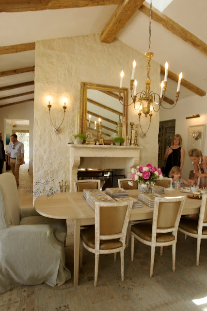 Dining room with gold, beams on ceiling and flowers on table