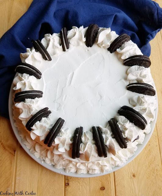 cake with piped whipped cream borders and cookie garnish