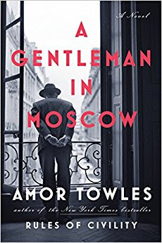cover art for A Gentleman in Moscow. Man in suit looking over a hotel balcony