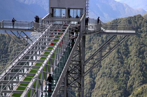 Tourists show off their check-in photo at newly opened glass bridge near Sapa