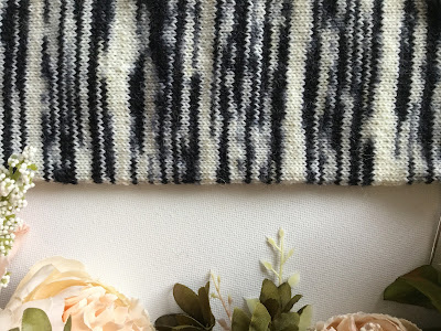 Zebra-striped knitted tube surrounded by peach flowers