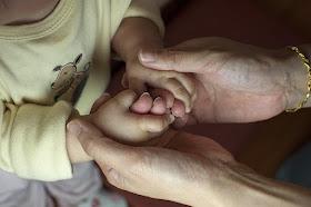 Hände einer Erwachsenen halten Kinderhände
