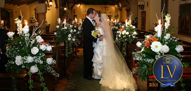 pareja de novios besándose en una iglesia de noche con arreglos florales y velas