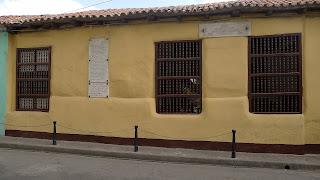 Santiago de Cuba, Geburtshaus des Dichters Heredia, gelbes Gebäude, Fenster mit den typischen Holzgittern, dunkelbraun gestrichen.