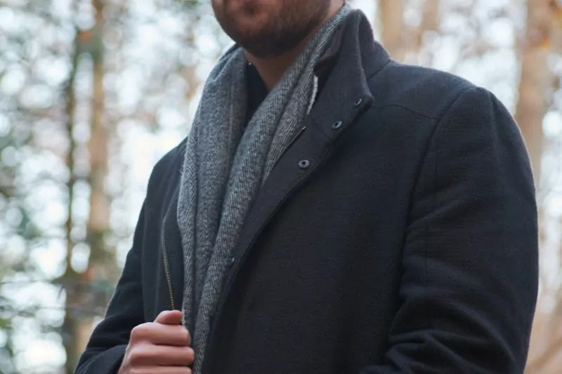 A men hide his scarf under coat.
