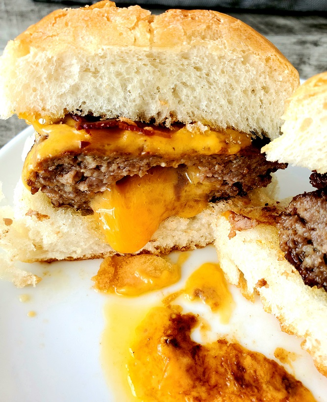 ground beef molded into a burger stuffed with extra sharp cheddar and oozing out the front