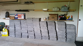 lots of bricks piled up in our garage for the patio