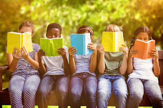 A row of children of different ethnicities sitting on a park bench, each reading a book