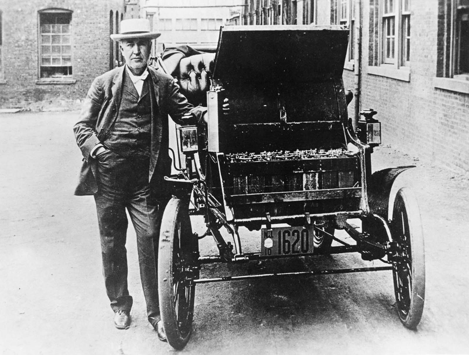 Thomas Edison poses with his first electric car, the Edison Baker, and one of its batteries. 1895.